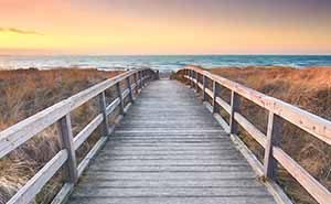 A boardwalk leading to the ocean at sunrise
